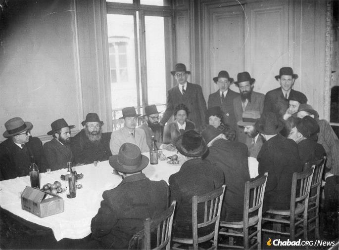 The Rebbe came to Paris in 1947 to meet his mother, Rebbetzin Chana there, this being their first reunion in 20 years. Paris is where Kahanov would first form a close relationship with the Rebbe. A Paris gathering in the Rebbe's honor: The Rebbe is seated fourth from the right, his mother next to him. Chaim Osher Kahanov is in the light-gray suit fourth from the left.
