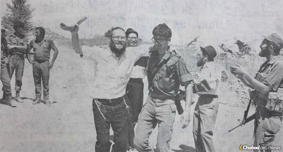 The Shofar Campaign was introduced by the Rebbe—Rabbi Menachem M. Schneerson, of righteous memory—in 1953. In the decades since Chabad emissaries and countless volunteers have brought the call of the shofar to street corners, public parks, hospitals, prisons and military bases. Rabbi Shmuel Greisman (center, holding shofar) can be seen bringing the shofar to Israeli soldiers during the month of Elul, 1980.
