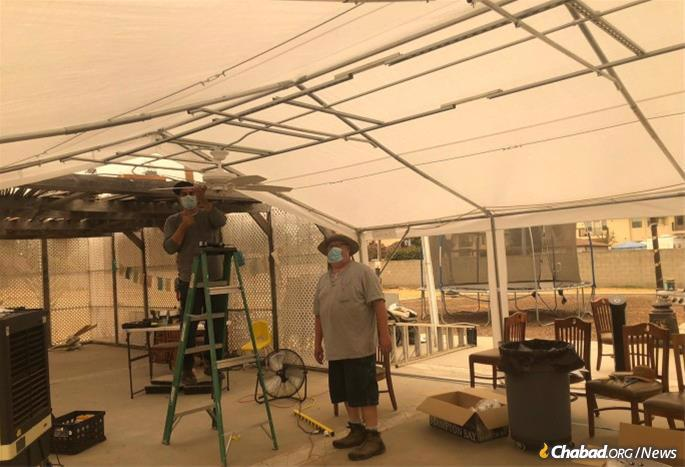 Workers putting up a tent for Rosh Hashanah at Chabad of Fresno, Ca. The sky above is red from fires consuming many areas along the U.S. West Coast.
