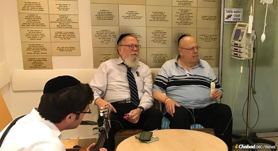 Never tiring, Avraham Lider, center, consistently came to the aid of Jewish community members before, during and after hospitalization. Here Lider and young volunteers visit patients at a New York City hospital.