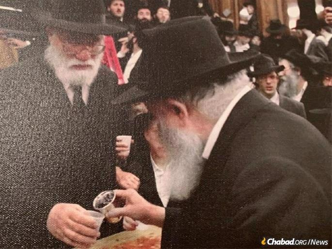 """Rabbi Ciment receives the """"cup of blessing"""" from the Rebbe following a farbrengen in 1990."""