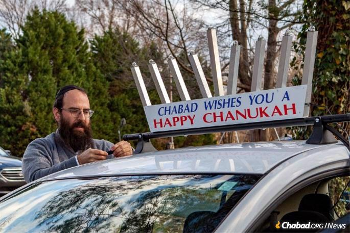 The Greensboro parade, which typically includes 40 vehicles, will wend its way from the local Chabad center, directed by Rabbi Yosef and Hindy Plotkin, to downtown where a giant menorah will be lit. Here, Rabbi Plotkin outfits his car. (Photo: Ivan Cutler)