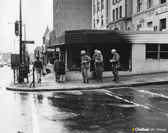 Members of the U.S. military stands watch on a street corner amid violence and rioting in Washington, D.C., 1968. (Credit: District Department of Transportation Historic Collections via Wikimedia Commons)