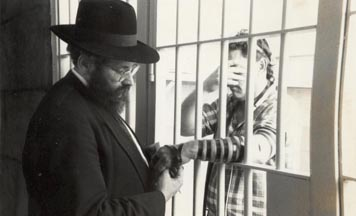 Rabbi Sholom Ber Lipskar, director of Aleph Institute, dons tefillin with an inmate