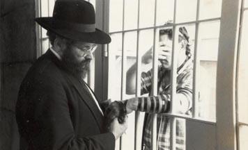 Rav Sholom Ber Lipskar, directeur du Aleph Institute, aide un détenu à mettre les Téfiline