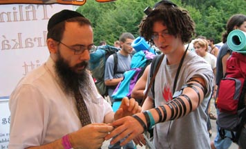 Rabbi Baruch Oberlander puts tefillin on a festival participant on Pepsi Island