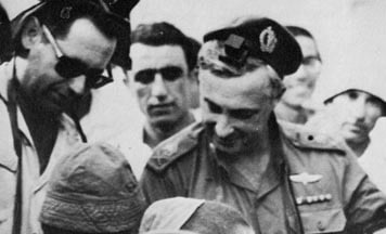Major General Ariel Sharon, Head of IDF's Southern Command during the Six Day War, puts on tefillin at the Western Wall