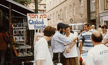 Chabad emissary assists a tourist with putting on tefillin