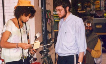 Chabad student on the streets of Katmandu assists a tourist with putting on tefillin