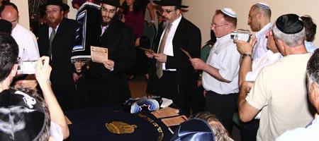 Rabbi Menachem Hartman (center), Chabad-Lubavitch emissary to Vietnam, Rabbi Mordechai Avtzon, and members of the Jewish community recite verses while greeting the new Torah written for the Jewish community in Vietnam.