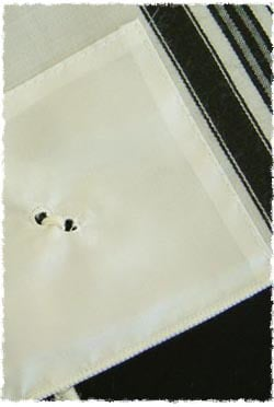 The two holes that the fringes are sprung through on the Tzitzit