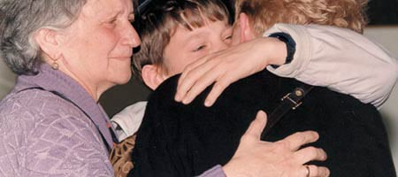 A child hugs his mother, with his grandmother looking on, prior to leaving Ukraine to Israel to be cared for by Chabad's Children of Chernobyl. Close to 80% of the children have been reunited in Israel with their family.