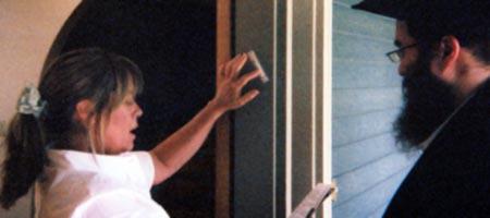 Susan Veeder from Garden Valley, Idaho affixes a Mezuzah on the doorpost of her home