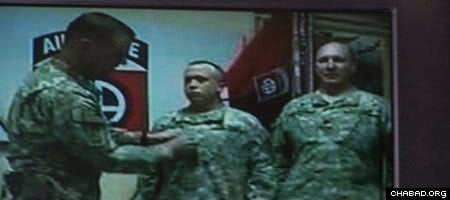 A screen shot of the presentation of Chaplain Shmuel Felzenberg's major insignia by Lt. Col. Brian McFadden, acting commander of the 82nd Combat Aviation Brigade stationed at Bagram Airfield in Afghanistan.
