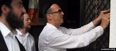 A Jewish resident of South Korea affixes a mezuzah to his door