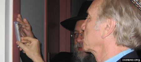 Sen. Joe Lieberman affixes a mezuzah to his new home's front door with the assistance of Rabbi Yisrael Deren.