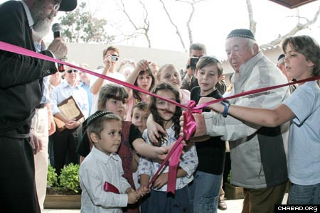Curitiba, Brazil's past meets its future as Holocaust survivor Naftali Steinberg joins a group of children in the ceremonial ribbon-cutting of the new Chabad-Lubavitch building. Rabbi Yoseph Dubrawsky, left, co-director of Chabad of Curitiba, looks on.