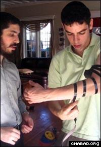 Rabbi Elie Estrin helps a student at the University of Washington put on tefillin.