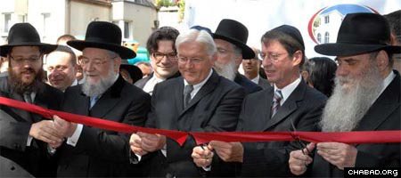 Rabbi Yehuda Tiechtel, left, Rabbi Israel Meir Lau, Foreign Minister Frank-Walter Steinmeier, Senator of Interior Erhart Koerting and Rabbi Moshe Kotlarsky cut the ceremonial ribbon to officially open the new headquarters of Chabad-Lubavitch of Berlin. Photo: Meir Dahan