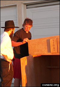 Rabbi Shmuel Fuss looks on as Andrew Malone inspects an antique ark.