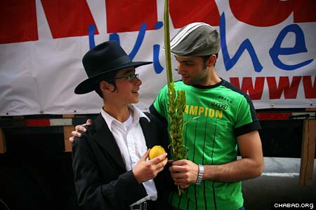 A passing New Yorker thanks a Chabad-Lubavitch rabbinical student for giving him to opportunity to make the blessing on the lulav and etrog. (Photos: Meir Alfasi)