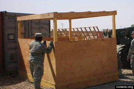 A serviceman positions the newly built sukkah on a waiting forklift.