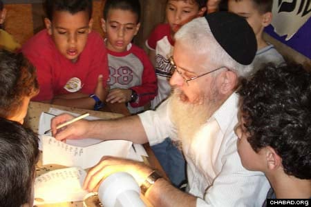 Children gather around a scribe as he demonstrates how one writes letters in a Torah scroll. (Photos: Meir Dahan)