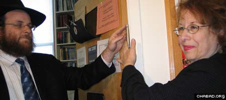 Rabbi Yonah Blum assists Columbia University professor Elizabeth Midlarsky affix a mezuzah to the doorway of her office, which last week was defaced with a swastika.
