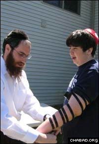 Rabbi Mendel Bendet helps a Jewish resident lay tefillin.