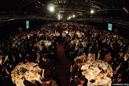 Hundreds of circular tables lined the Pier 94 ballroom as close to 4,500 Chabad-Lubavitch emissaries, their parents and supporters enjoyed an evening of elegant food, inspiring speeches and moving video presentations as part of the grand banquet at the International Conference of Chabad-Lubavitch Emissaries. (Photos: Israel Bardugo)