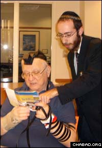 Rabbi Chesky Tenenbaum puts on tefillin with Martin Hershkowitz, who told the rabbi about the chaplaincy opening.