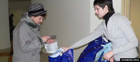 A volunteer hands out a filled package at Moscow's Shaarei Tsedek Charity Center