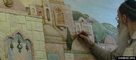 Michoel Muchnik, a Lubavitch Chasid and artist, adds some color to one of his paintings.
