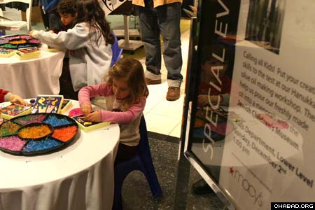 A child works on a Chanukah art project during the Jewish Children's Museum Chanukah workshop at the Macy's department store in Manhasset, N.Y. (Photos: Eli Kahn)