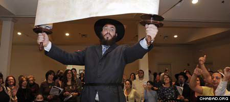 Members of Metairie, La.'s Jewish community look on as the Chabad Jewish Center's new Torah scroll is hoisted for all to see.