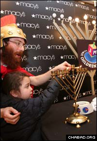 Judah the Maccabee teaches a child how to light the Chanukah menorah at a display at the Macy's flagship department store on Manhattan's 34th Street.