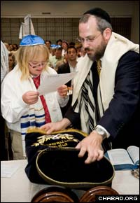 Wesley Baer, left, who despite having Down syndrome completed a year of studying Hebrew, Jewish history and Judaism with Rabbi Yitzchok Magalnic , co-director of Chabad-Lubavitch of Palos Verdes, Calif., recites the blessings over the Torah at his bar mitzvah.