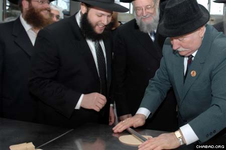 Lech Walesa tries his hand at rolling matzah during a visit to a factory in Kfar Chabad, as Rabbi Shalom DovBer Stambler, director of Chabad-Lubavitch of Poland, offers some guidance. Former Israeli Chief Rabbi Israel Meir Lau stands next to Walesa.