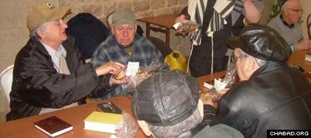 Safed residents mark the holiday of Tu B'Shevat at the Eshel Binyamin soup kitchen operated by Colel Chabad.