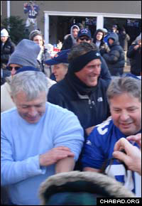 After putting tefillin on himself, New York Giants fan Jay Greenfield, right, assists others in donning the sacred items.