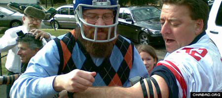 A helmeted Rabbi Yossi Deren, co-director of Chabad-Lubavitch of Greenwich, Conn., helps New York Giants fan David Katz put on tefillin at a tailgating party in Roslyn, N.Y.