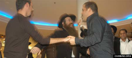 Rabbi Nechemya Wilhelm of Chabad of Bangkok-Ohr Menachem in Thailand dances with two Israelis during Chabad-Lubavitch of Thailand's 12th annual reunion party in Jerusalem.