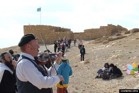 A violinist sets the mood for a mass bar and bat mitzvah celebration organized by Chabad-Lubavitch of Ramat Hasharon, Israel, for some 600 of the town's seventh-graders. The ceremony took place atop the country's mountaintop fortress of Masada.