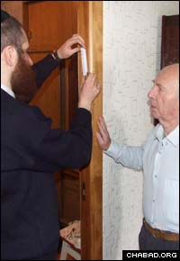 A Chabad-Lubavitch rabbi affixes a mezuzah to the doorpost of a home in Dnepropetrovsk, Ukraine.