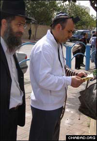 Assisted by a Chabad-Lubavitch rabbi, a resident of Ashkelon, Israel, puts on tefillin after a series of Palestinian rocket attacks paralyzed the coastal city.