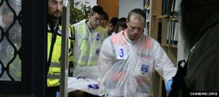 Workers with Israel's ZAKA organization, which ensures proper burial of Jewish remains, remove one of the eight murdered students from Jerusalem's Mercaz Harav yeshiva Thursday night.