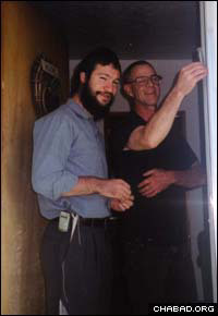 Chabad-Lubavitch Rabbi Zalman Mendelsohn helps a Jewish resident of Wyoming affix a mezuzah to his doorpost.