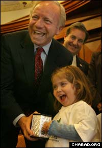 A student from the preschool operated by Chabad-Lubavitch of Greater Boynton Beach, Fla., presents a charity box to Connecticut Sen. Joseph Lieberman.