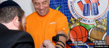 Rabbi Berl Goldman, co-director of the Lubavitch-Chabad Jewish Student & Community Center serving the University of Florida, helps University of Tennessee basketball coach Bruch Pearl lay tefillin.