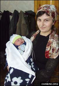 An alumnus of the STARS Jewish educational program in Tashkent, Uzbekistan, holds her newborn son soon after his ritual circumcision.
